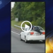 Man Rides On Back Of Moving Car On The Highway – VIDEO