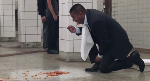 man eats pasta off subway florr