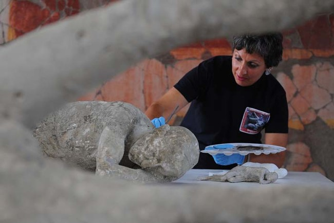 A restorer cleans and analyses a petrified victim of the eruption of Vesuvius volcano in 79 BC, as part of the restoration work and the study of 86 casts in the laboratory of Pompeii Archaeological Site, on May 20, 2015 in Pompeii.   AFP PHOTO / MARIO LAPORTA        (Photo credit should read MARIO LAPORTA/AFP/Getty Images)