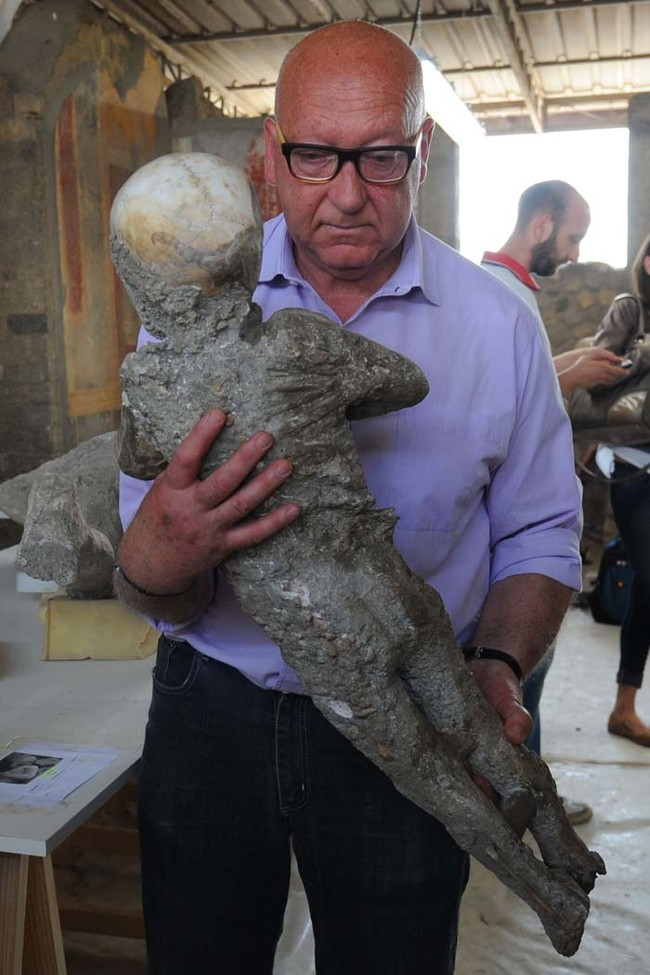 Stefano Vanacore, director of the laboratory of Pompeii Archaeological Site, carries a petrified victim of the eruption of Vesuvius volcano in 79 BC, during the restoration work and the study of 86 casts, on May 20, 2015 in Pompeii Archaeological site.   AFP PHOTO / MARIO LAPORTA        (Photo credit should read MARIO LAPORTA/AFP/Getty Images)