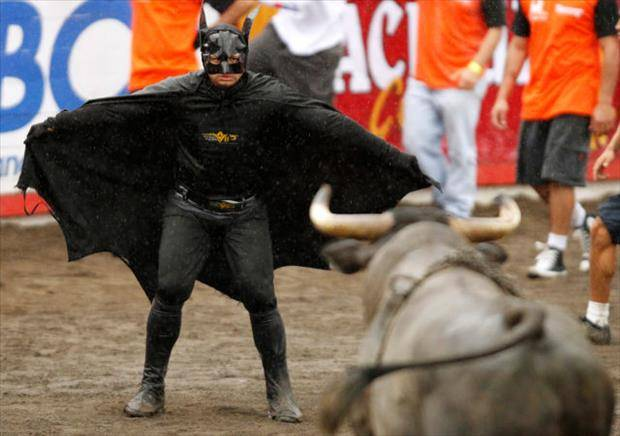 A man wearing a Batman costume gestures towards a bull in an improvised bullring during the annual bullfight festival in Zapote, near San Jose December 30, 2010. More than 350 bullfighters participated in the traditional end of year bullfight. REUTERS/Juan Carlos Ulate (COSTA RICA - Tags: SOCIETY ANIMALS TRAVEL IMAGES OF THE DAY)